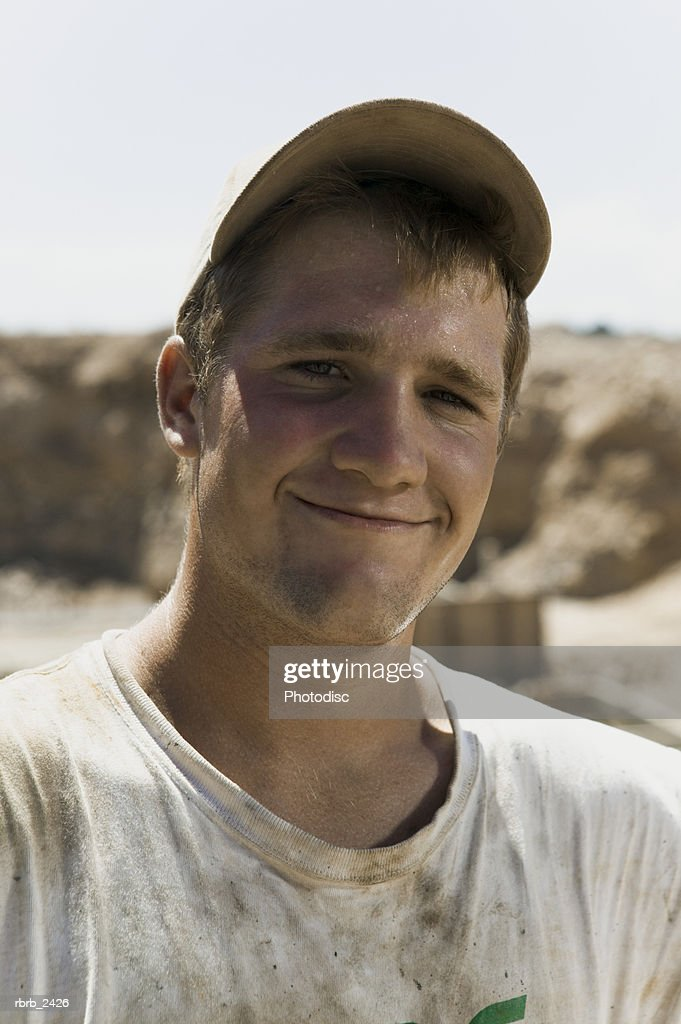 lifestyle shot of an adult male in work clothes and a ballcap as he smiles at the camera : Foto de stock