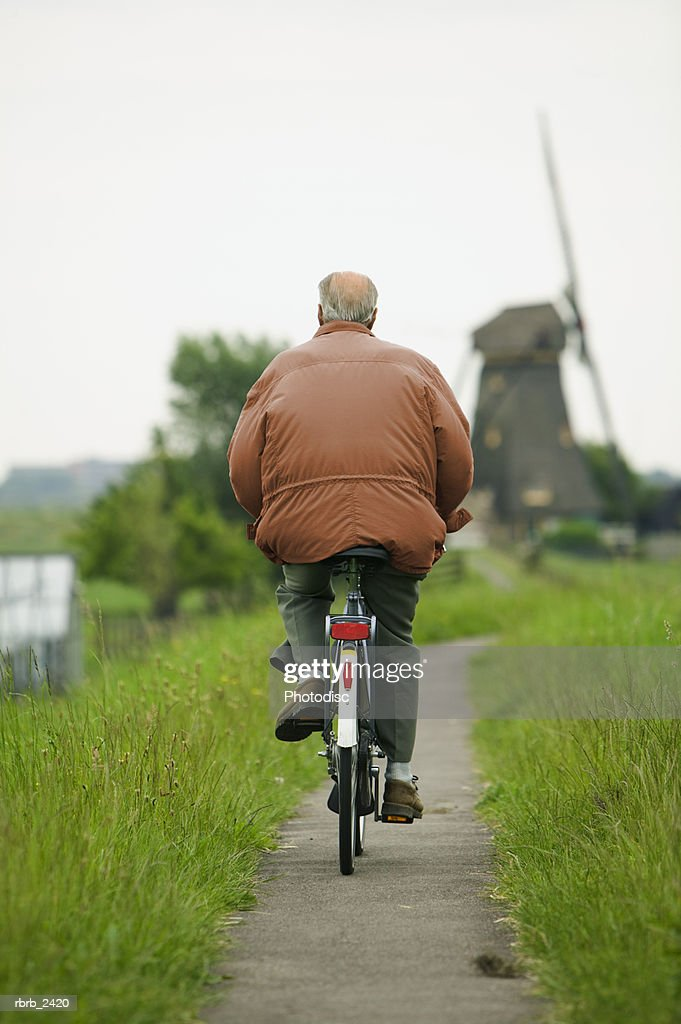 lifestyle shot of an adult man as he rides his bike down a path by an old windmill : Stockfoto