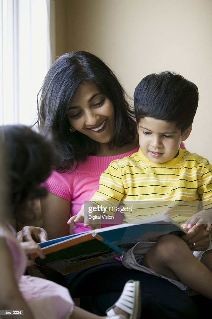 lifestyle shot of an adult mother as she reads to her young children : Foto de stock