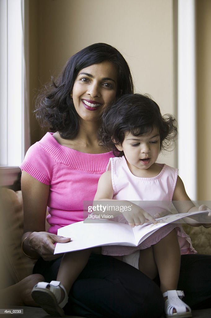 lifestyle shot of an adult mother as she reads to her young daughter : Foto de stock