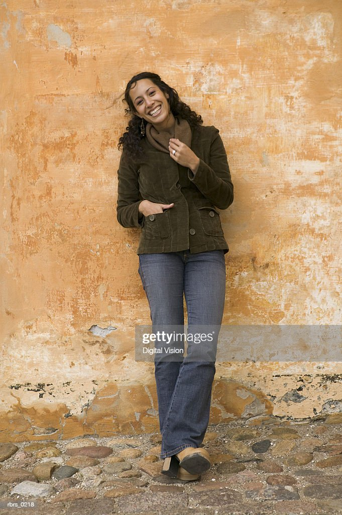 lifestyle shot of an young adult female as she leans against an orange wall and smiles : Foto de stock