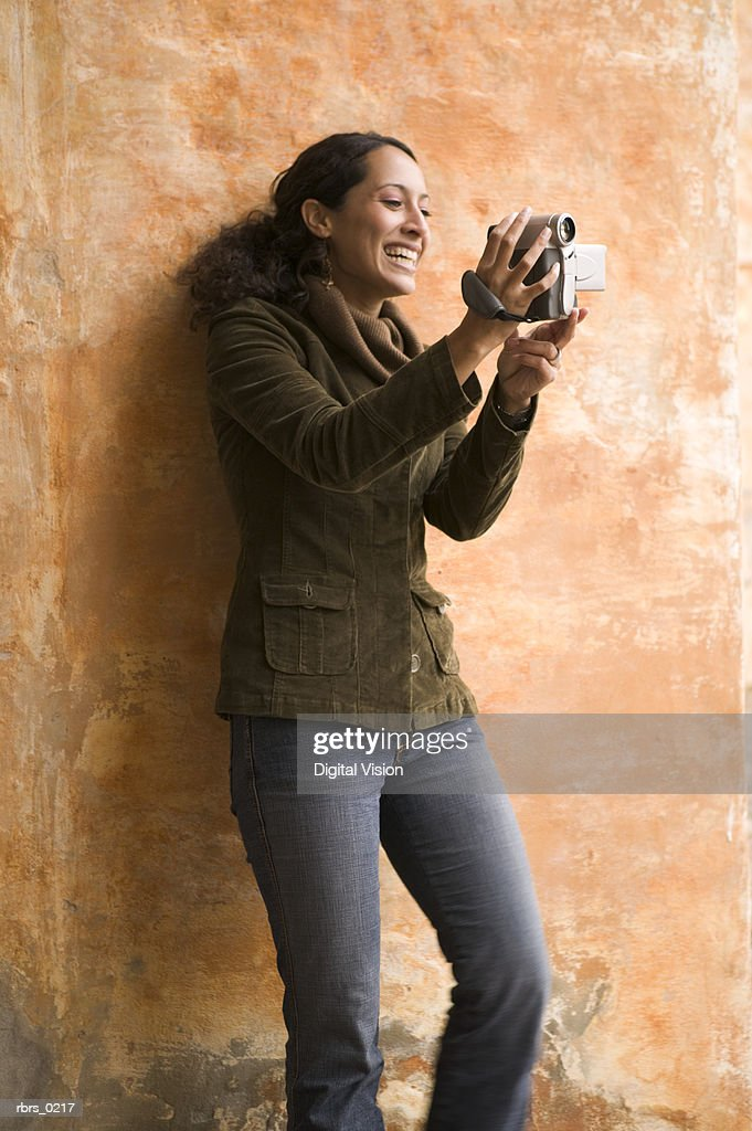 lifestyle shot of an young adult female as she plays with a video camera : Foto de stock