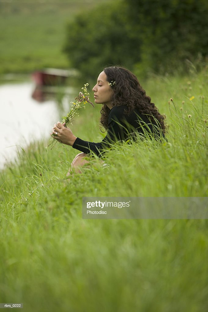 lifestyle shot of an young adult female as she sits by a brook and picks wild flowers : Foto de stock