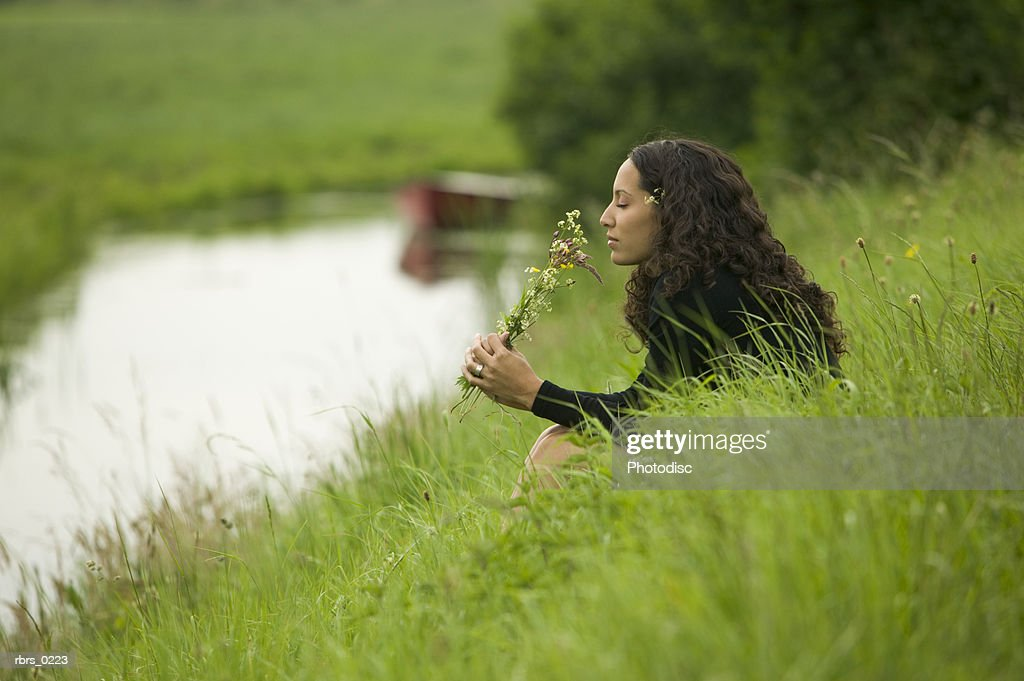 lifestyle shot of an young adult female as she sits by a brook and holds wild flowers : Foto de stock