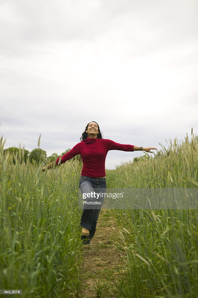lifestyle shot of an young adult female in a red sweater as she runs through a tall grass field : Foto de stock