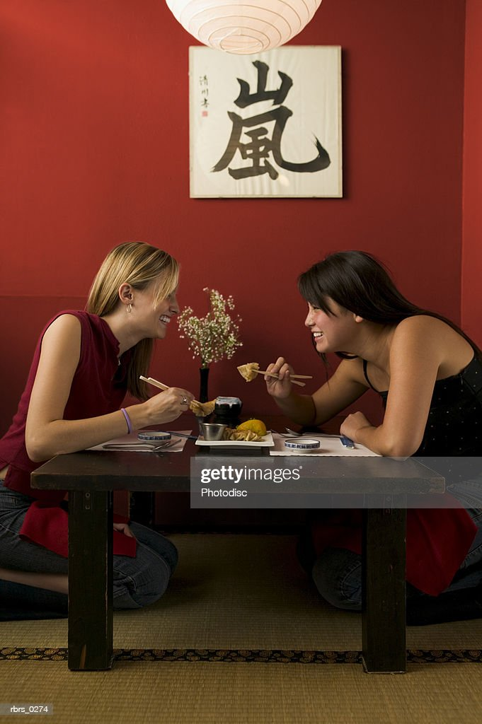 lifestyle shot of two teenage girls as they eat out together at a chinese restaurant : Foto de stock