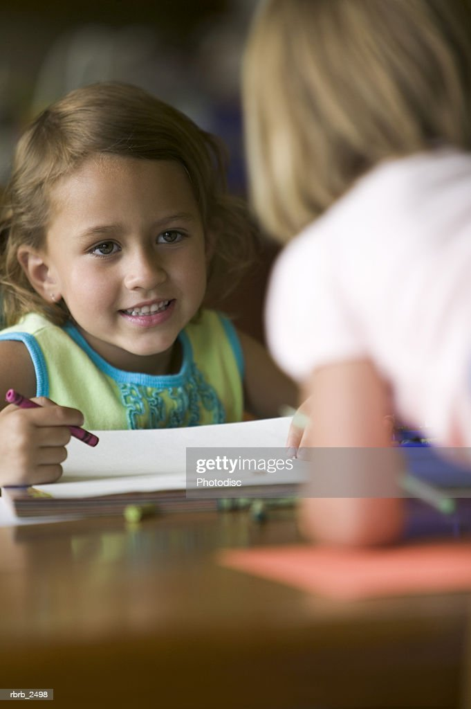 lifestyle shot of two young sisters at they sit at a table drawing and coloring pictures : Foto de stock