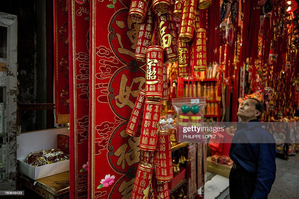 Lifestyle-Asia-offbeat-Lunar, FEATURE by Beh Lih Yi A man looks up to in front of a shop selling Chinese New Year decorations in Hong Kong on February 5, 2013. A stock market slide, possible conflict between Japan and China and more Gangnam-styled success for South Korean singer Psy will shape the incoming Year of the Snake, say Asian soothsayers. AFP PHOTO / Philippe Lopez