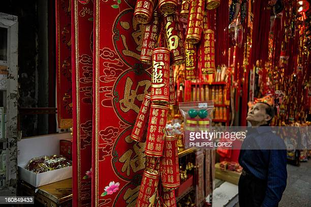 LifestyleAsiaoffbeatLunar FEATURE by Beh Lih Yi A man looks up to in front of a shop selling Chinese New Year decorations in Hong Kong on February 5...