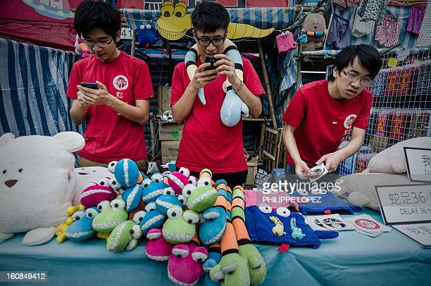 LifestyleAsiaoffbeatLunar FEATURE by Beh Lih Yi Youths check their phones as they stand at a stall of a Chinese New Year fair in Hong Kong on...
