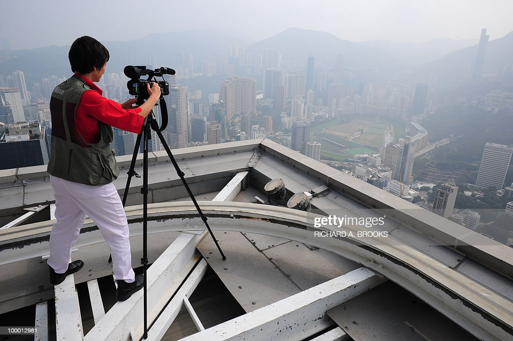STORY 'Lifestyle-HongKong-China-environment-air-pollution' BY POLLY HUI This photo taken on December 2, 2009 shows an AFP journalist taking video footage of the Happy Valley area of Hong Kong, surrounded in haze as air pollution again covers the territory. On top of Victoria Peak in Hong Kong, groups of tourists find themselves staring at an apocalyptic vision of a towering city shrouded in a menacing grey smog.