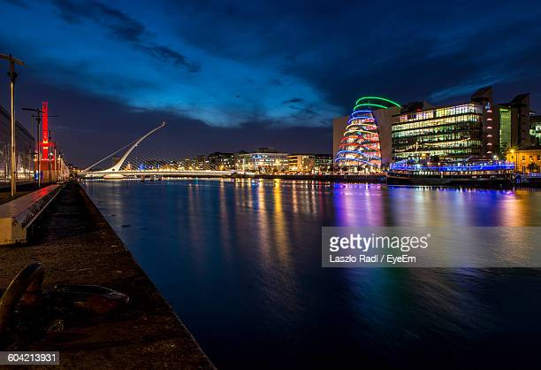Liffey River By Illuminated Modern Buildings In City Against Sky