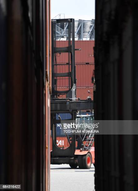 A lift moves among containers at Oi container yard of the Tokyo port in Tokyo on May 18 2017 Japan has posted its longest economic expansion in over...