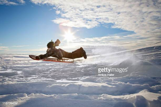 lift off on a sled - tobogganing stock pictures, royalty-free photos & images