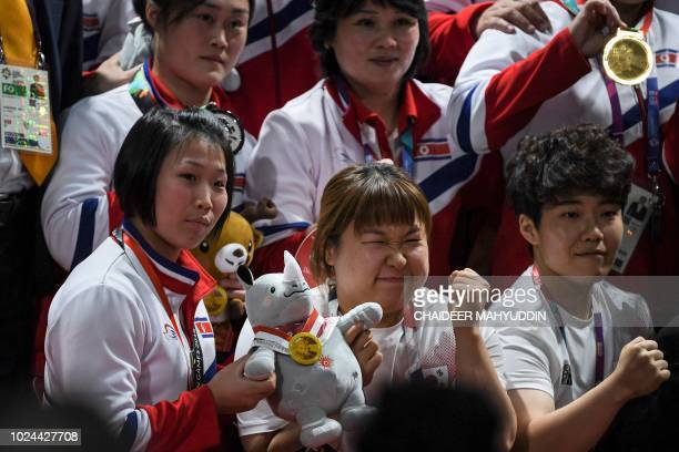 Lifters from North and South Korea take a group photo during the awards ceremony for women's 75kg weightlifting event during 2018 Asian Games in...