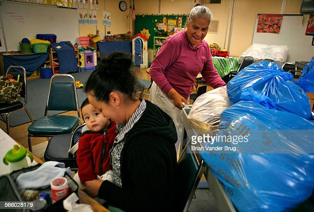 Liggett Street Elementary School parent center volunteer Dolores Garcia right rolls in with bags of bread and bagel donations for needy parents at...