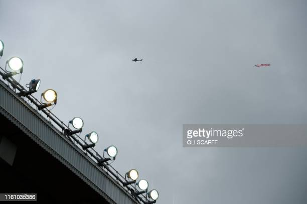 TOPSHOT A light aircraft flies over the stadium pulling a Glazers Out slogan during the English Premier League football match between Manchester...