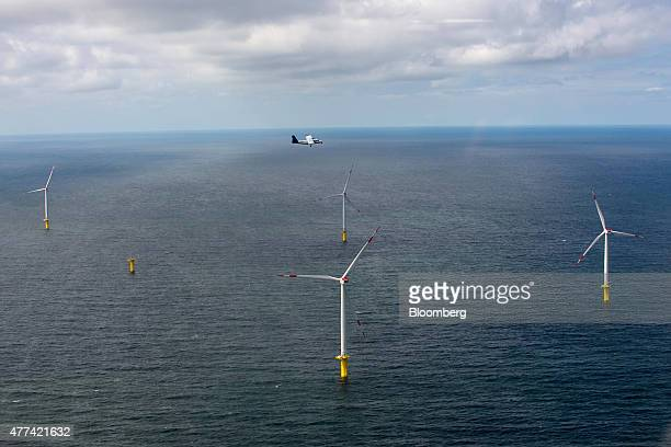 A light aircraft flies over wind turbines in the North Sea as installation and construction continues at Amrumbank West offshore wind park operated...