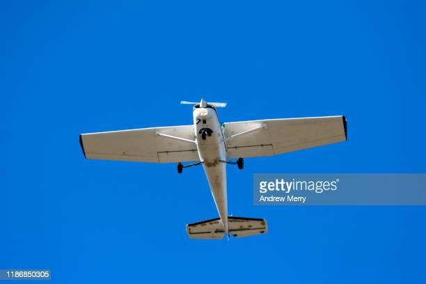 light aircraft flying overhead at takeoff with blue sky - air vehicle stock pictures, royalty-free photos & images