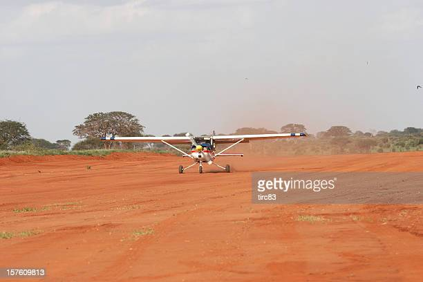 light aircraft taking off from kenyan bush airstrip - airfield stock pictures, royalty-free photos & images