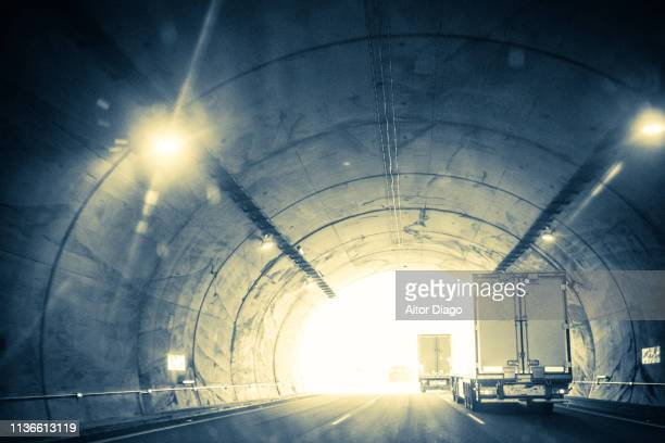 Light at the end of the tunnel. Traffic of trucks and cars through a tunnel. Image moved and with a retro style