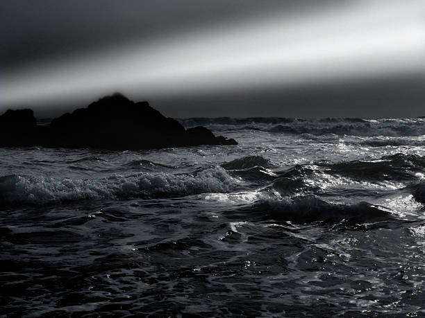 A light beam over rocky shore and water