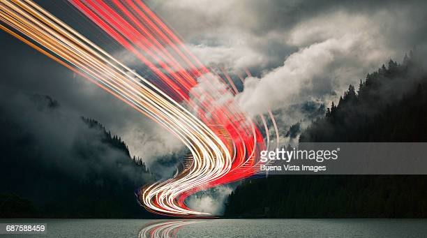 light beams over a mountain lake - digital composite stock-fotos und bilder