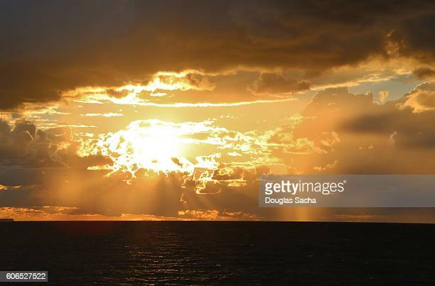Light beams penetrate the clouds as the sun rises over the ocean