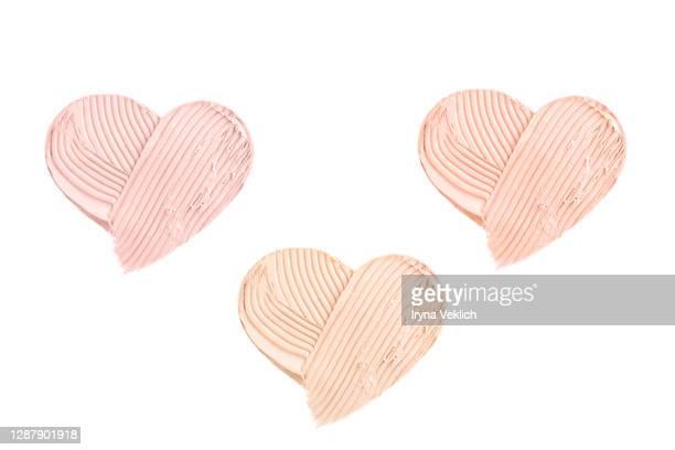 light beige smears of creamy foundation in shape of heart. - 頬紅 ストックフォトと画像