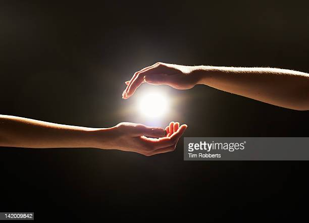 light between hands. - femme entre deux hommes photos et images de collection