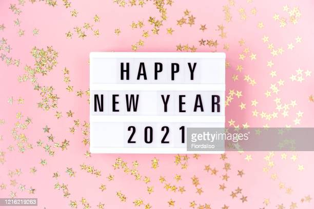 light box inscription happy new year 2021on pink background - 2021 stock-fotos und bilder