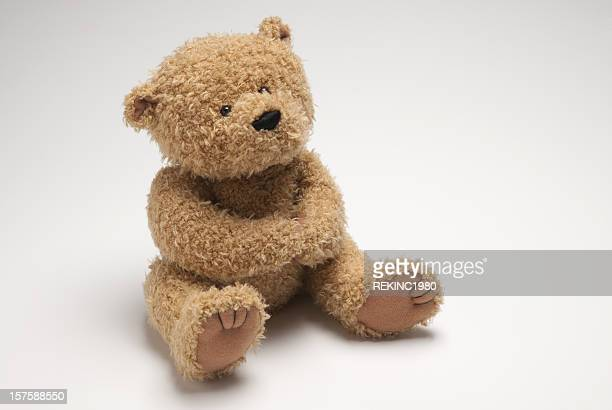 Light brown stuffed bear sitting on white surface