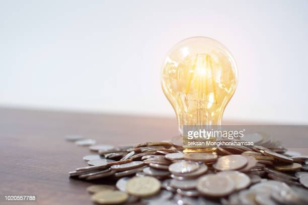 light bulb and pile of coins with copy space - money fotografías e imágenes de stock