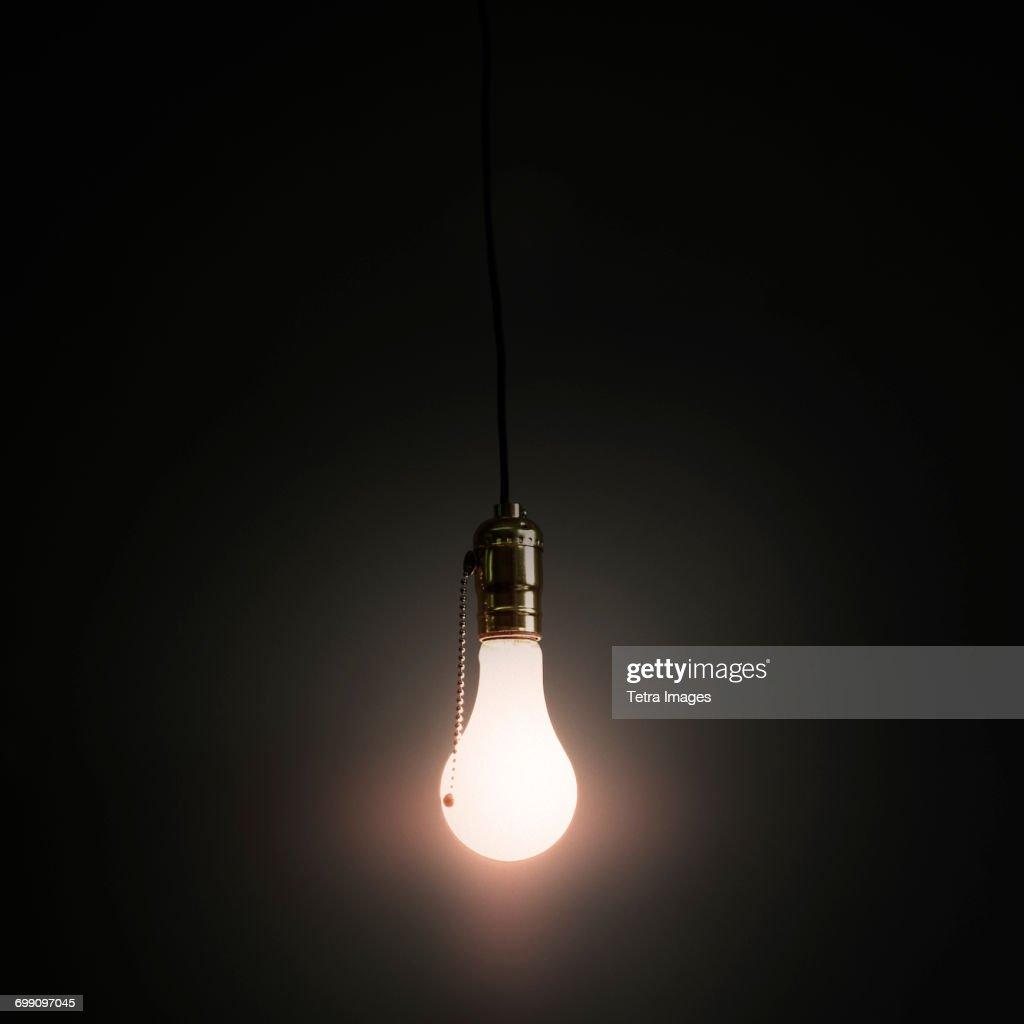 Light bulb hanging against grey background stock photo getty images light bulb hanging against grey background stock photo aloadofball Choice Image