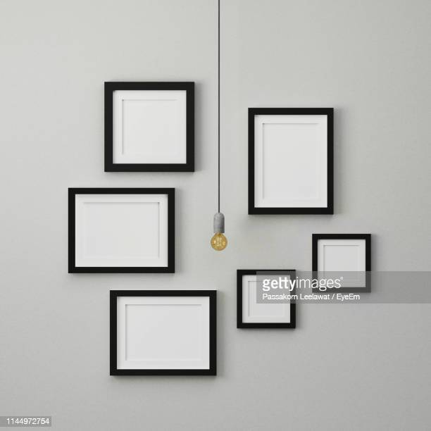 light bulb hanging by empty picture frames on white wall - cuadrado composición fotografías e imágenes de stock