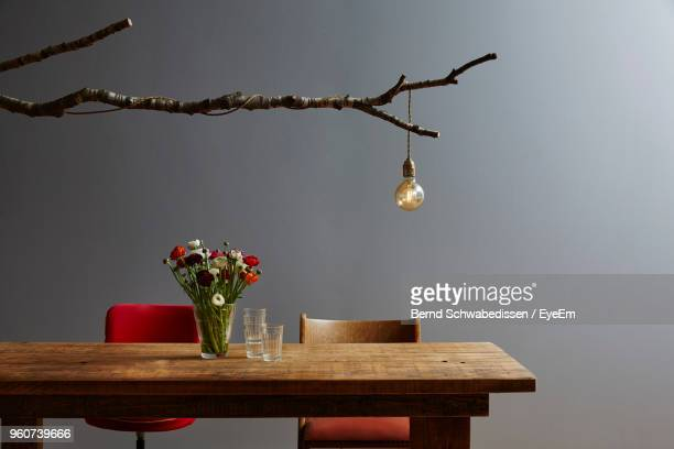 light bulb hanging on wood over dining table against wall - tavolo da soggiorno foto e immagini stock