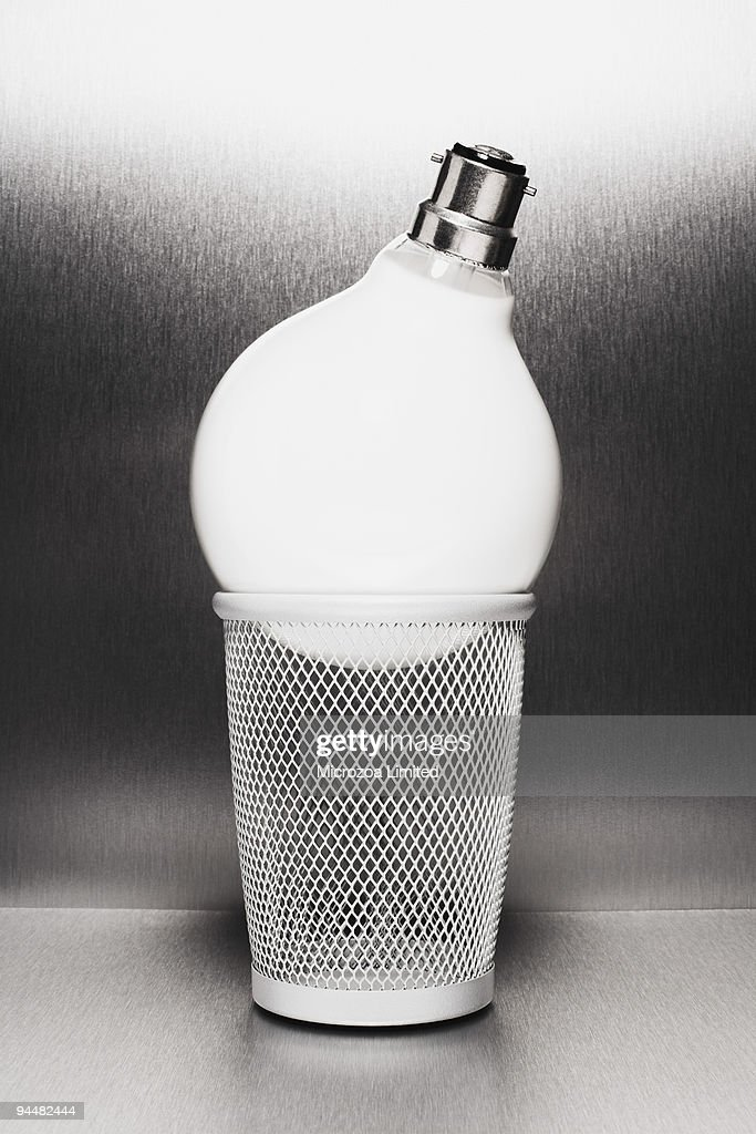 Light bulb in trash can : Stock Photo