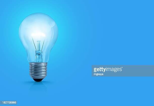 light bulb on blue background - light bulb stock pictures, royalty-free photos & images