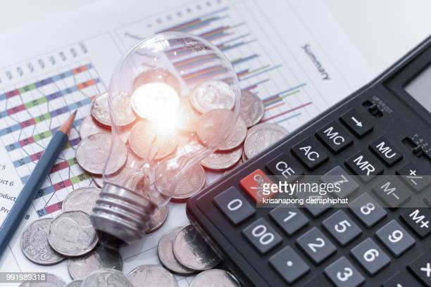 light bulb with coins and calculator on documents
