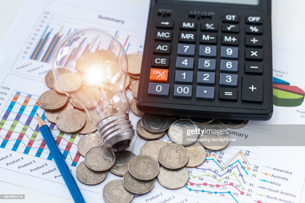 light bulb with coins and calculator on documents : Stock Photo