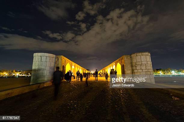 light cascades from iwans lining the khaju bridge onto families and friends celebrating nowruz iranian new year. - ハージュ橋 ストックフォトと画像