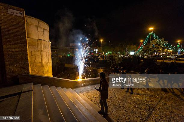 Light cascades from iwans lining the Khaju Bridge onto families and friends celebrating with fireworks during Nowruz Iranian New Year.