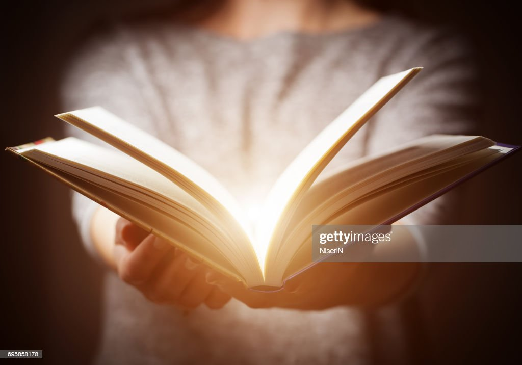 Light coming from book in woman's hands in gesture of giving : Stock Photo