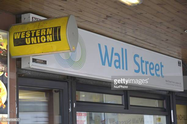 Light emitting from the sign of Western Union in Manchester on Monday 30th March 2015 Western Union based in the United States is a multinational...