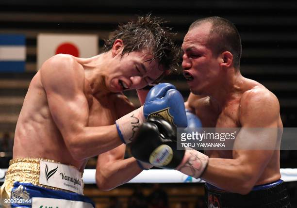 Light flyweight champion Ryoichi Taguchi of Japan fights with IBF light flyweight champion Milan Melindo of Philippines during the eleventh round of...
