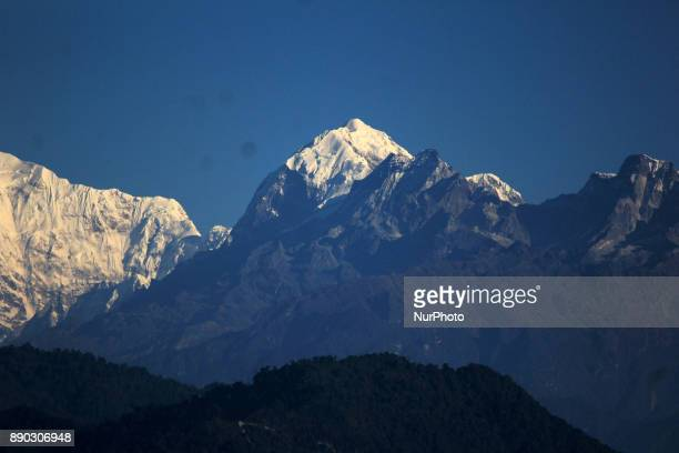 Light from a sunrise is cast on mountain Kangchenjunga near Darjeeling on December 11 2017 Kangchenjunga is the third highest mountain in the world...
