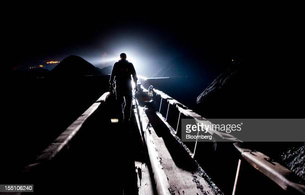 A light from the American Electric Power Co's AEP Leader towboat silhouettes a deck hand as he walks on barges loaded with 30000 tons of coal during...