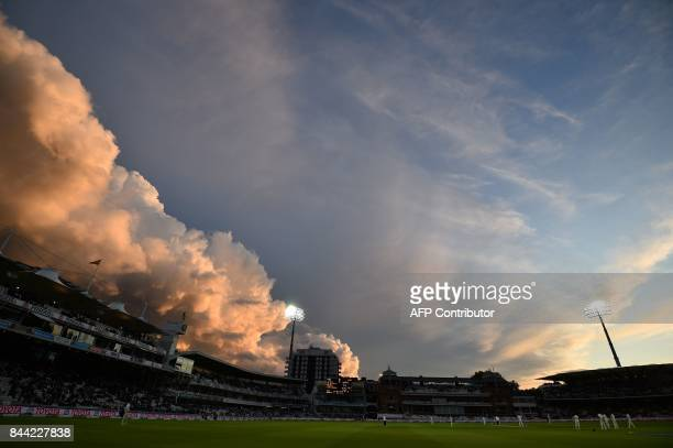 Light from the setting sun catches the clouds above Lords cricket ground in London on September 8 2017 during the second day of the third...