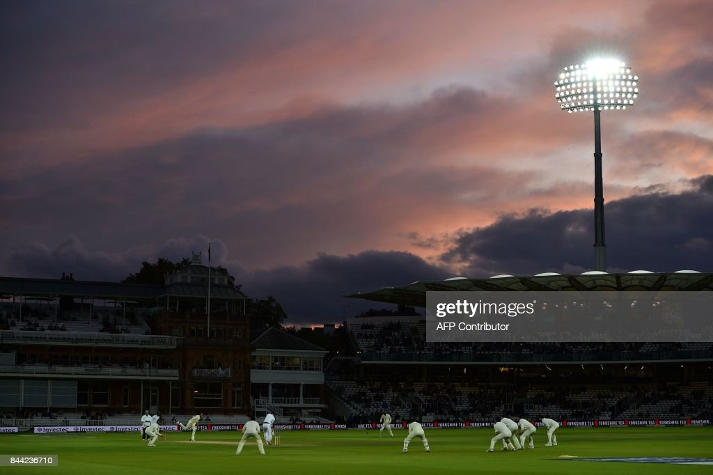 Light from the setting sun catches the clouds above Lords cricket ground in London on September 8, 2017 as England's Stuart Broad bowls during the second day of the third international Test match between England and West Indies. / AFP PHOTO / Glyn KIRK / RESTRICTED