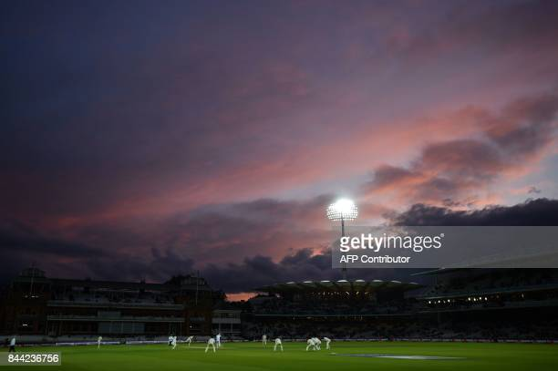 Light from the setting sun catches the clouds above Lords cricket ground in London on September 8 2017 as England's Stuart Broad bowls during the...